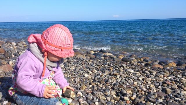 Augustinchen sitzt am Meer und spielt mit Steinen.